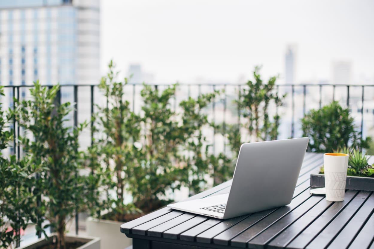 Homeoffice draußen, Laptop auf Balkontisch mit Pflanzen im Hintergrund
