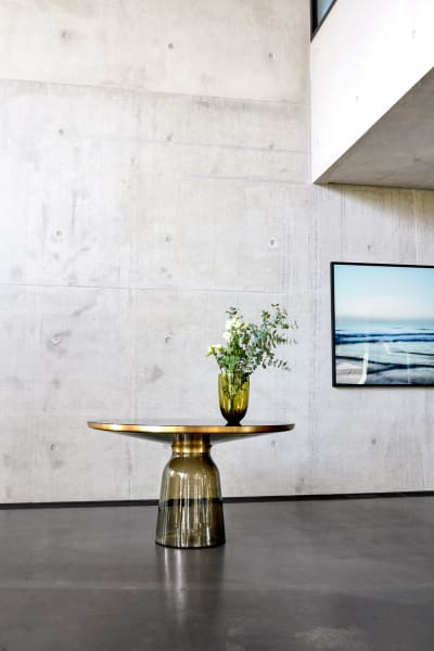 """Filigrane Neuheit – Sebastian Herkners """"Bell"""" für ClassiCon gibt es nun auch als Esstisch. Der Fuß, der eine gläserne Glocke anmuten soll ist aus dünnem mundgeblasenem Glas, darauf balanciert eine Platte aus Messing."""