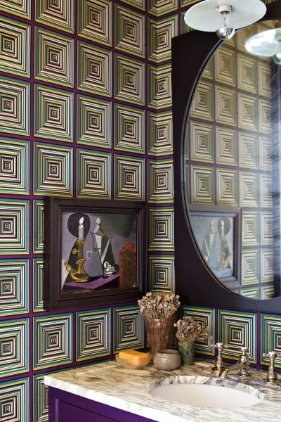 Im Gästebad schafft ein eingebauter Waschtisch mit Marmorplatte optisch Ruhe, die leicht psychedelische Tapete (von Secondhand Rose) und das Gemälde in gleichem Kolorit geben dem Raum Persönlichkeit.