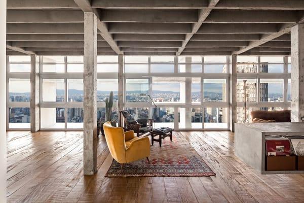 """Zwischen Himmel und Erde: Für diesen 20 Meter breiten Panoramablick auf        die Metropole kaufte Regisseur André Godoi die Nachbarwohnung dazu. Als        Kinosessel dienen der """"Jangada""""-Stuhl von Jean Gillon und ein gelber        Vintage-Sessel. Der Teppich ist von À la Garçonne."""