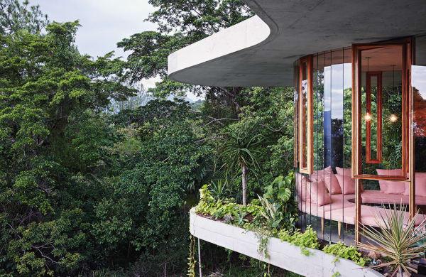 Organischer Schwung: Das Haus liegt auf einer Bergkuppe, die Wohnetage zwischen den gekurvten Betonscheiben wurde zum Tal hin zudem aufgeständert.