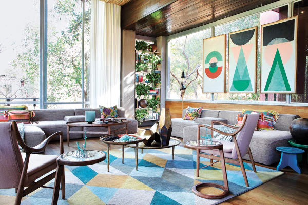 Formenreichtum: Die Sofas im Salon erinnern an flache Landschaften,        konterkariert von den organisch geschwungenen Holzlehnen der Finn        Juhl-Sessel. Weiße Leinenvorhänge schaffen einen ruhigen Rahmen.