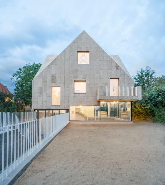 Das Fassadenraster des Hauses spielt mit unregelmäßig gegeneinander versetzten Fensteröffnungen.