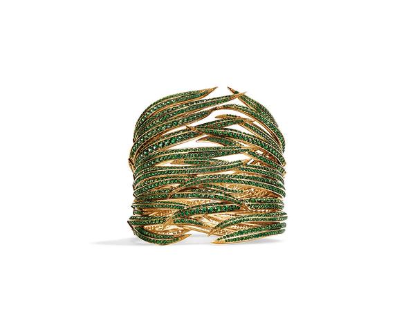 Mit erbsengrünen Tsavoriten ausgefasst, winden sich die Goldblätter des        Cuffs um den Arm, an den Spitzen blitzen gelbe Saphire.