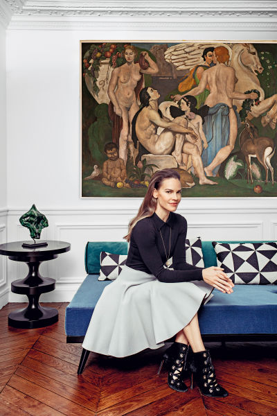 Hollywood (Regency) trifft auf Pariser Chic: Hilary Swank wirkt (in Azzedine Alaïa und Schmuck von Cartier) französisch kokett. Das Daybed entwarf ihr Interiordesigner Axel Huynh und bezog es mit Samt von Dedar. Hinter ihr ein malerischer Reigen vom Flohmarkt. Tischchen: India Mahdavi.