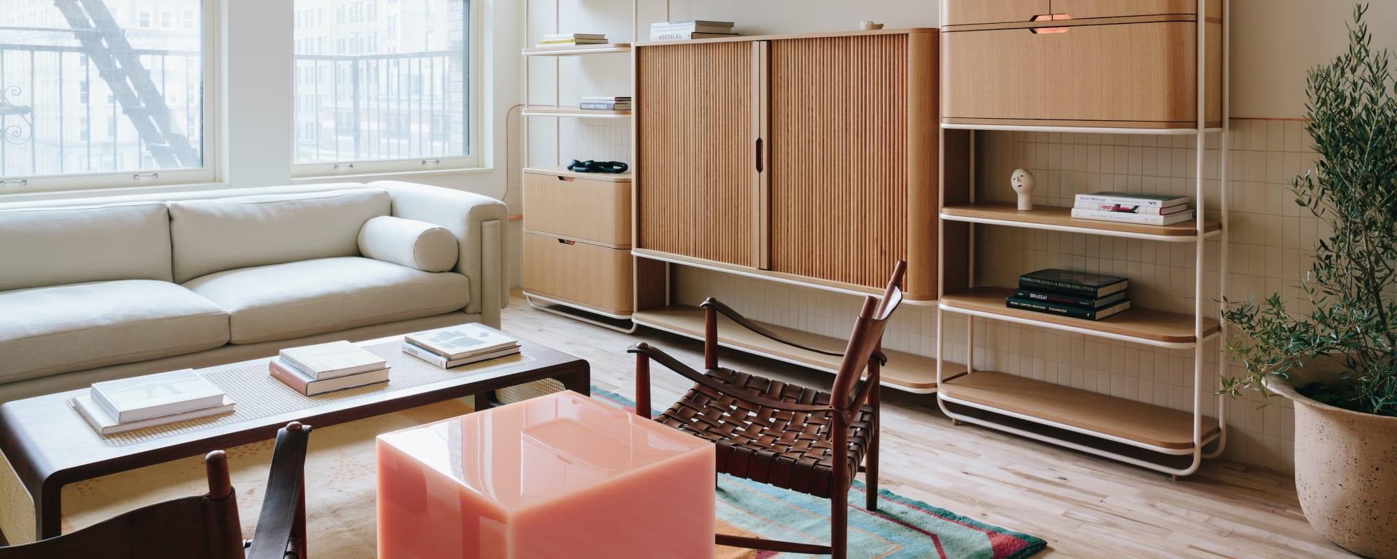 Blick ins Wohnzimmer mit hellem Sofa und einem Rosa Würfel aus Kunstharz
