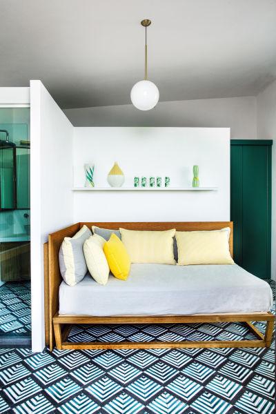 Das Bett im kleineren Haus trennt eine halbhohe Wand vom Bad. Deckenleuchte von Flos.