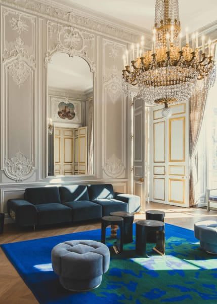 """Der Salon des Aides de Camp datiert aus dem Jahr 1720, die Boiserien sind original. Von Lemaire stammen das tiefblaue Sofa """"Garment"""", ergänzt mit vier seiner """"Hellmet""""-Tische aus geschwärzter Bronze."""