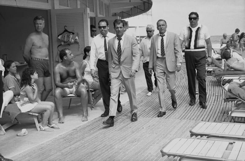 Frank Sinatra mit Bodyguards und seinem Double (er trägt die gleiche Kleidung wie Sinatra) bei Dreharbeiten, 1968