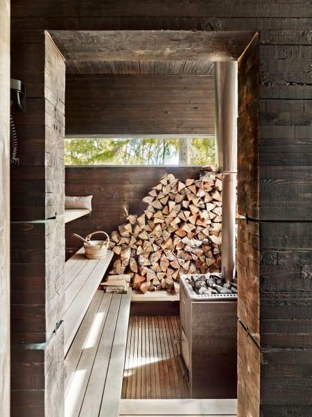 Die urtümlich anmutende holzbeheizte Sauna in Schweden wurde aus geteerten Fichtenbalken errichtet.