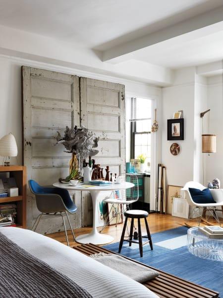 Den Wohn- und Schlafraum links teilen sich Midcentury-Ikonen von Saarinen, Eames und Noguchi mit einer Flohmarkt-Tür und dem Kartell-Coffeetable der Brüder Bouroullec.