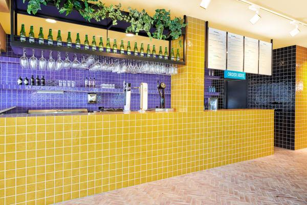 Für die Bar setzte das Designstudio auf glasierte Keramikfliesen in Senfgelb und Lila.
