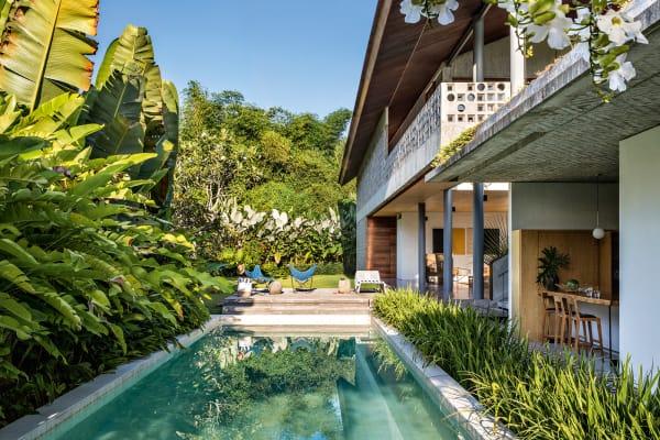 Schwimmen unter Orchideenzweigen. DieRumah Panjang macht ihrem NamenLanges Haus alleEhre: Der Riegel misst 50 Meter und wird von einem Kühle spendenden Pool flankiert. Vom Obergeschoss mit seinen drei Gästezimmern kann man bei guter Sicht den Vulkan Gunung Agung sehen.