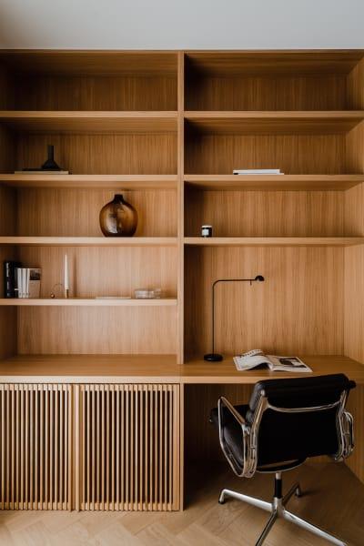 """Mit Farbe, Form, Material lassen sich Homeoffices bestens ins Private eingliedern, ein Bürostuhl jedoch macht aus jedem Tisch einen Arbeitsbereich. Aber da Schreibtischarbeit schon vor Corona die meisten Rücken beugte, sollte man auch beim Heimarbeiten die Ergonomie berücksichtigen: Ein höhenverstellbarer Schreibtisch mag nicht immer möglich sein, aber ein für die Muskulatur optimierter Bürostuhl, ein Bildschirm auf Augenhöhe, externe Maus samt Tastatur oder zumindest ein Laptopgestell sind allemal realisierbar – und wie die polnische Interiordesignerin Agnieszka Owsiany zeigt, ist das keine Entscheidung zwischen schön oder gut. Der lederne """"Soft Pad Chair"""" von Eames schenkt dem Eichen-Einbau eine mondäne Mad-Men-Grandezza."""