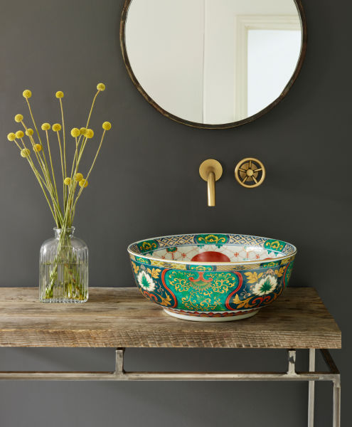 """Buntes Treiben im Bad. Mit der Keramik """"Adriana"""" kommt Farbe ins Bad. Ein Kunstwerk, ein handbemaltes Porzellanbecken, dessen Außenseite mit einem detailreichen Muster auf smaragdgrünem Untergrund leuchtet. Ein schöner Kontrast dazu: das Innere ist in weißem Porzellan belassen und mit kunstvollen Blüten und Ornamenten in Rottönen verziert."""
