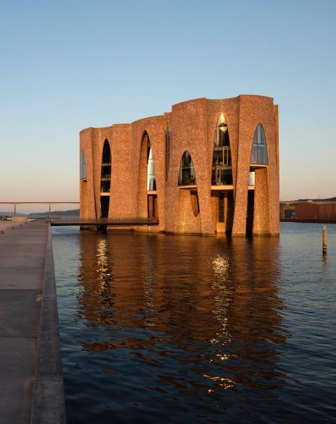 Olafur Eliassons Gebäude für Kirk Kapital dient gleichzeitig als Pionierbau für die Belebung des Hafenquartiers und verbindet in seiner Architektur gleichzeitig die Typologie der Hafengebäude mit den Farbspektren des Meeres.