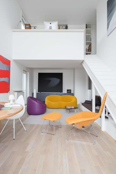 Sein Büro ließ er oben ohne. Die Öffnung schenkt nun auch dem Living Luft und Licht und den runden Möbeln, wie dem Sofa und dem Sessel von Pierre Paulin (erhältlich über Ligne Roset), einen rechten Rahmen. Das Sideboard schuf der Hausherr ebenso das schwarze Bild, das eine Lichtprojektion bespielt.