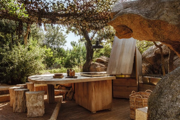 Ein Esszimmer unter freiem Himmel samt Außenküche gestalteten Les Ateliers Lebon aus Iroko-Holz.