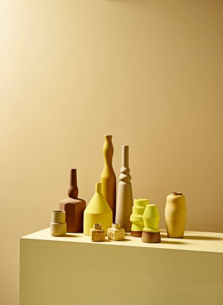 """Gelb und Haselnuss. V.li.: """"Small Vase Beige"""" von Nobel Design über Bon Ceramics, 45 Euro. Vier Keramikgefäße """"Le Morandine V."""" von Sonia Pedrazzini, zwischen 110 und 150 Euro. Zwei Mini-Vasen mit Glasur aus isländischer Vul- kan-Asche von Bjarni Sigurdsson Ceramic, je 30 Euro. Braun-gelbe Steinzeuggefäße von Martin Schlotz, je 160 Euro. """"Curve"""" von Karin Blach Nielsen, 188 Euro. Fond: Little Greenes """"Stone-Mid-Warm Absolute Matt Emulsion"""", 42 Euro / Liter. Block: """"Hay No. 37"""" von Farrow & Ball, 81 Euro / 2,5 Liter."""