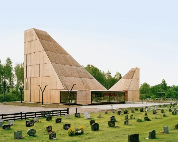 """""""Das Projekt begann mit einem Inferno!"""" Denn: Ein Feuer brannte die alte        Kirche in Våler nieder. Surnevik errichtete einen pyramidalen Neubau aus        Pinienholz und schuf – so der norwegische Volksmund – eine """"Kathedrale        des Waldes""""."""