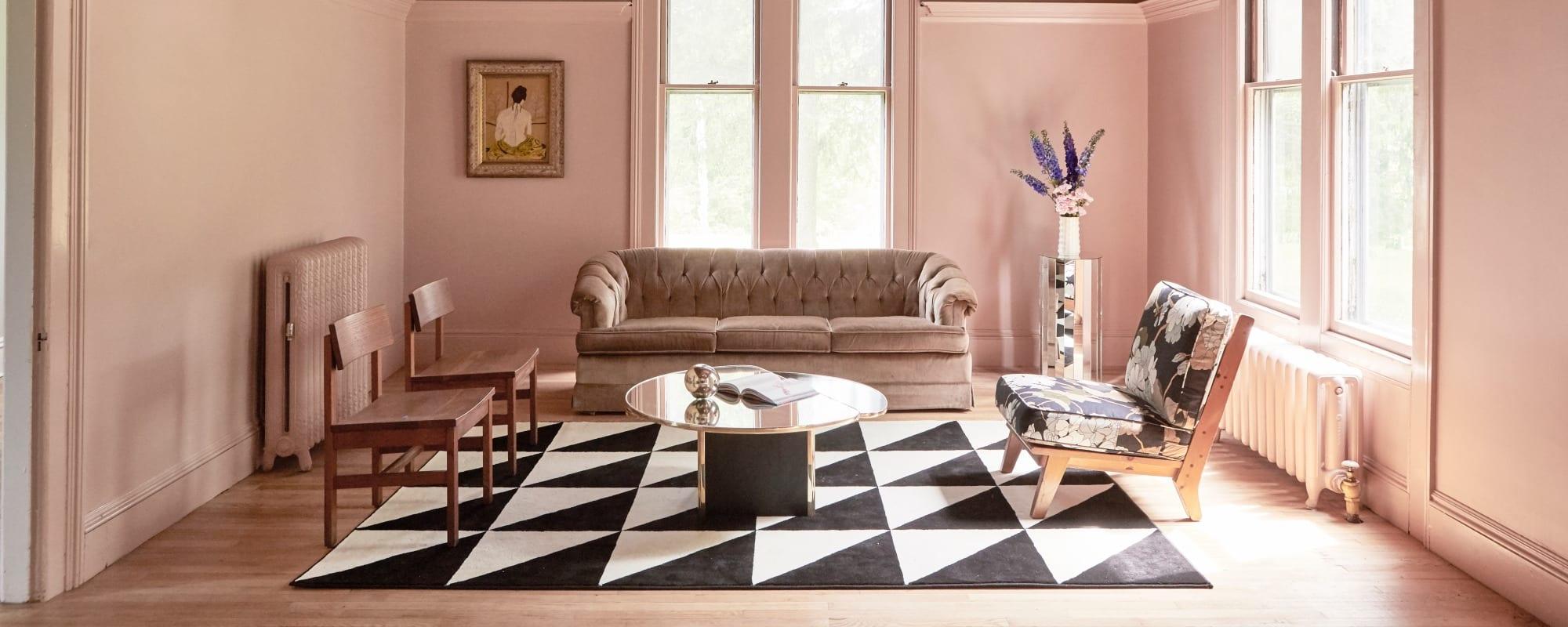 Ein in altrosa getünchtes Zimmer mit zwei Stühlen, einem Sofa und einem Sessel, die auf einem Teppich mit Zickzack-Muster stehen.