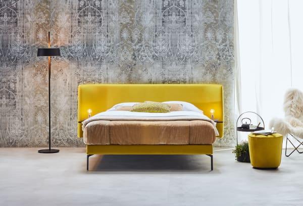 """Auch bei grauen Wintertagen strahlt das eigens von Angela Schramm designte Bett """"Brace"""" in einem Sonnengelb. Durch die Metallfüße und die niedrige Höhe wirkt das Bett grazil und bringt Leichtigkeit in den Raum."""