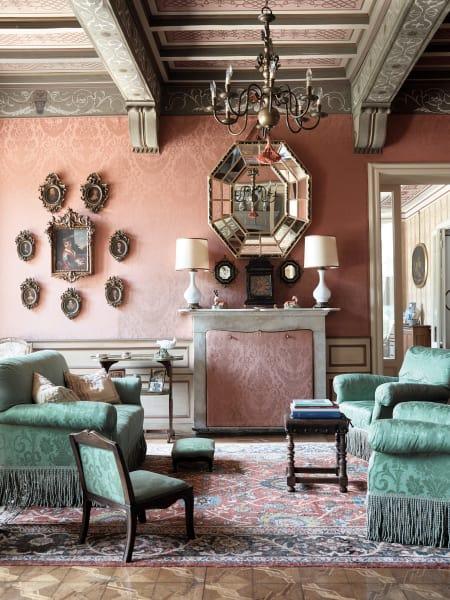 Der kleine Kamin im roten Salon wird nicht mehr genutzt – im Spiegel sieht man die Reflexion des großen an der rückwärtigen Wand. Links davon gruppieren sich um das Bildnis eines unbekannten Künstlers diverse Ahnenporträts der Familie Castelbarco Albani Gropallo.
