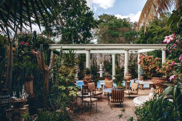 Auferstanden aus Ruinen: Klassische Säulen, die dem Pool einen        hoheitsvollen Rahmen geben, werden von schmiedeeisernen Gartenmöbeln und        einem in Chinoiserie emaillierten Tisch kontrastiert, die Maag in        Connecticut kaufte.