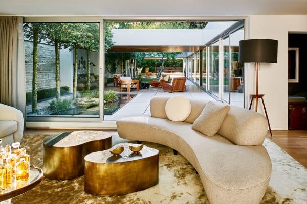 Vom Wohnzimmer aus wirkt das Haus besonders offen und        großzügig. Die Bronzetische sind Sonderanfertigungen des New Yorker        Künstlers Silas Seandel, der als einziger Modern Americana-Designer noch        heute entwirft. Stehleuchte: BDDW.