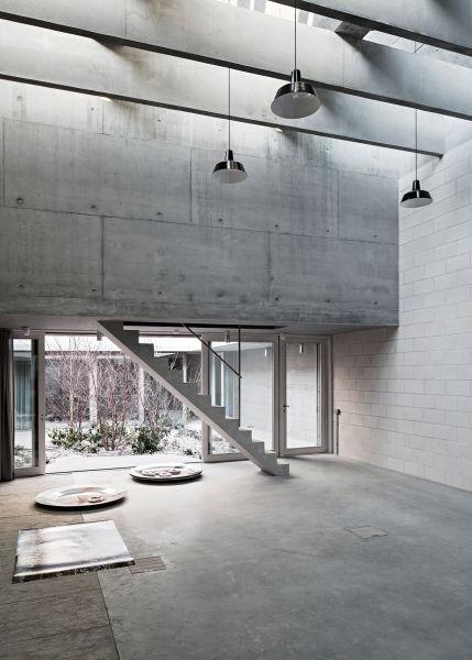 Der mittlere Bau ist das Herz von Tellers neuem Studio. Direktes Tageslicht gibt  es nicht. An beiden Enden des Gebäudes sind scheinbar frei an der Decke hängende Würfel untergebracht, die als zusätzlicher Lagerraum dienen – und die Treppen als  ideales Motiv, um Menschen dort zu inszenieren.
