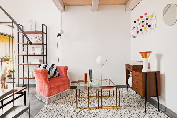 """Der Wohnraum als Wundertüte: Von Eames' """"Hang it all"""" über eine        Tischleuchte von Anastassiades für Flos bis zur Ananas aus Muranoglas        findet alles seinen Platz. Das Zackenkissen ist von Kenzo Home."""