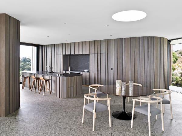 """Beim Mobiliar stezten die Architekten ebenfalls auf Holz udn entschieden sich für die Barhocker """"Morph"""" vonZeitraumund Vintage-Stühlen vonNiels Bendtsen, der Tulip-Tisch vonKnoll International."""