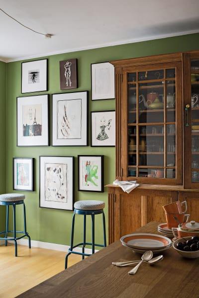 """Wenn Jasmin Khezri in der Küche sitzt, blickt sie auf Farrow & Balls        """"Yeabridge Green"""" und ihre eigenen Werke: """"Das fühlt sich für mich        behaglich an."""" Die Ikea-Barhocker wurden mit Kissen von Pierre Frey        veredelt. Der Schrank stammt von einem Londoner Flohmarkt, das Geschirr        ist von Royal Copenhagen."""