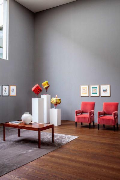 Martin Kippenbergers Papierarbeiten kommen im Oberlichtsaal mit Franz Wests Pappmaché-Skulpturen ins Gespräch. LuisLaplace hat die sorbetrosa SamtsesselaufLauschposten gestellt und den Raum mit perlgrauem Leinenausgeschlagen.