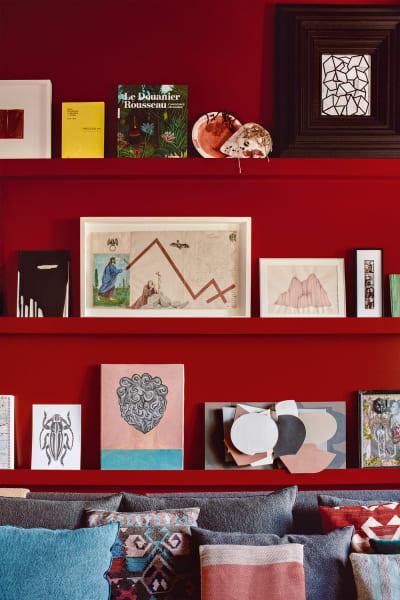 Das Fernsehzimmer tauchte Paloma Cañizares ganz in Rot. Rechte Seite: Den Tisch mit integrierter Buchstütze entwarf die Architektin selbst und arrangierte darauf die Bilboquet-Spielfiguren ihres Großvaters. Passende Stühle kommen von Studio Zaven für Atipico.
