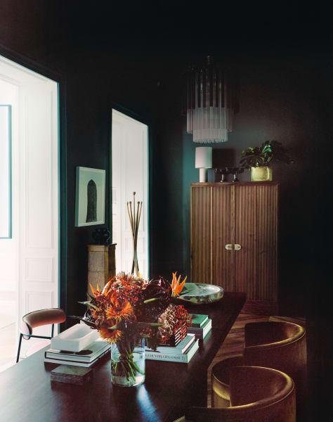 """Für das dunkle Kabinettentwarf er die Stühle und den Barschrank aus Wurzelholz. An der Wand: Roni Horns Fotografie """"Untitled, No. 4""""."""