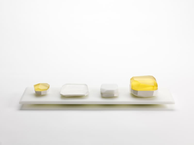 Andrea-Walsh,-Collection-of-Faceted-Boxes-on-a-White-Glass-Plinth,-2013.-Fine-Bone-China-and-Kiln-Cast-Glass