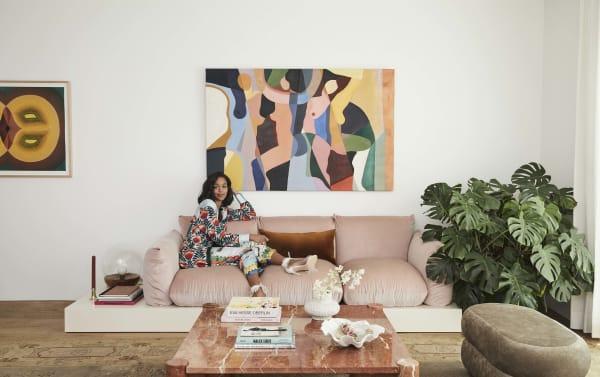 Die Schauspielerin Laura Harrier sitzt im Schlafanzug von Oscar de la Renta auf ihrem Vintage-Sofa. Um es an ihre Körpergröße anzupassen – sie ist 1,76 m groß – und einen Beistelltisch hinzuzufügen, baute die Innenarchitektin Tiffany Howell eine schwebende Plattform darunter. Gemälde von Jessalyn Brooks. Fashion Styling von Danielle Goldberg.