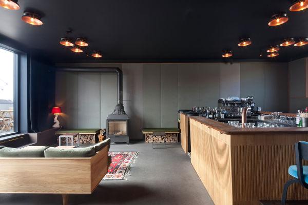 """Herzstück des """"Flushing Meadows"""" Hotels: Die Bar! Hier harmoniert ein Vintage-Sofa (neu bezogen mit waldgrünen Kvadrat-Stoff) mit der Bar aus Eiche und ausgewählten Vintage-Pieces."""