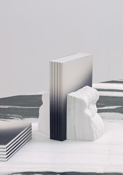 Wie an einen Fels, können sich Bücher oder Magazine an die Sklupturale Stütze aus Marmor anlehnen,