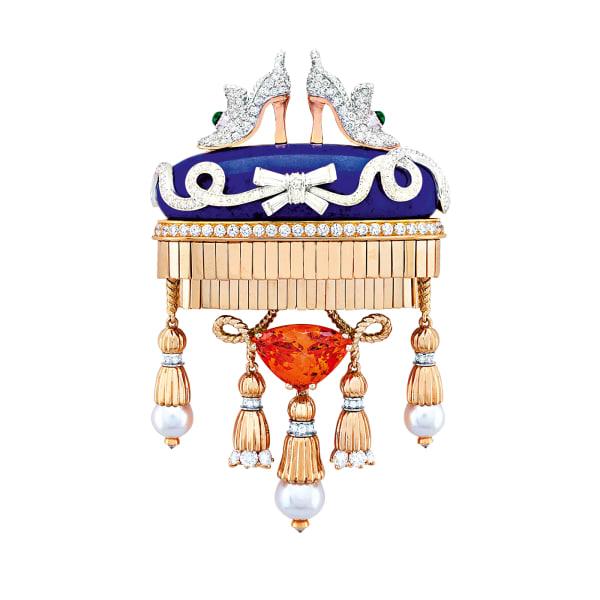"""Und das Herz der Prinzessin? Hängt an einem Spessartin-Granat im Troidia-Schliff! Aber ihre Schuhe thronen auf einem Lapislazulikissen mit Diamantschleife, an dessen Goldschnüren Perlenpompons baumeln. Die Brosche """"Souliers précieux"""" fasst das Märchen der Brüder Grimm in Edelsteine."""
