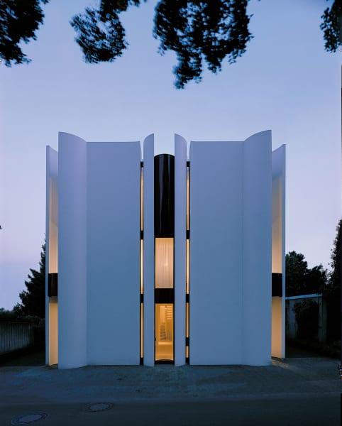 Als seien es Paravents, umschließen Halbschalen den grazilen Bau in Bad      Nauheim. Mit seiner konsequenten Eckenvermeidung eckte der Architekt      Hölzinger damals ganz schön an. Am Ende des Eingangs führt eine geschwungene Treppe nach oben.