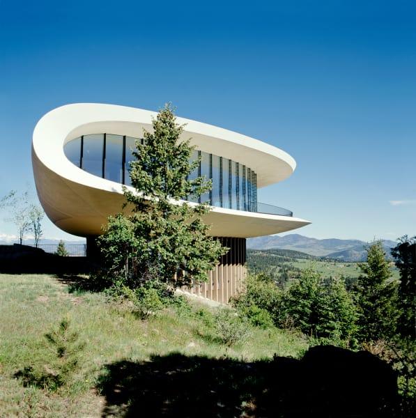 """Die auffallend futuristische Form des """"Sleeper House"""" thront auf einem Hang und überragt die beeindruckende Landschaft."""