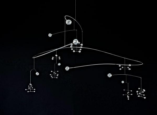 """Für ihr anmutiges """"Glass Mobile"""" tariert die in        Maastricht lebende Designerin Anne Büscher große und kleine Murmeln aus        – so lange, bis sie in himmlischer Balance schweben. Dabei lässt das        gläserne Sternbild ahnen: Das Universum kann vielleicht doch wieder ins        Gleichgewicht gebracht werden! Unikate, Preise auf Anfrage."""