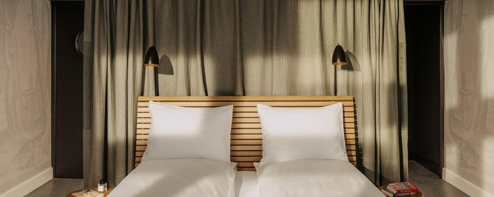 Frontalansicht eines Bettes im Hotelzimmer, dahinter ein blassgrüner Vorhang.