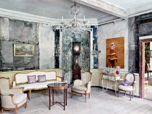 Der Salon im Erdgeschoss trägt Reste handbemalter Leinenbahnen aus dem 18. Jahrhundert, provisorisch gesichert durch Fliegengitter. Das intarsierte Kinderporträt ist eine Arbeitvon Tilo Uischner.
