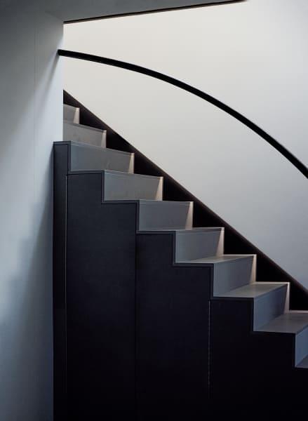 Zu Höherem: Die Treppe, die in die obere Ebene führt ist, genauso wie der Boden in der übrigen Wohnung, mit Pietra Serena ausgelegt, einem Sandstein mit besonders feiner Körnung. Das Geländer besteht aus Stahl.