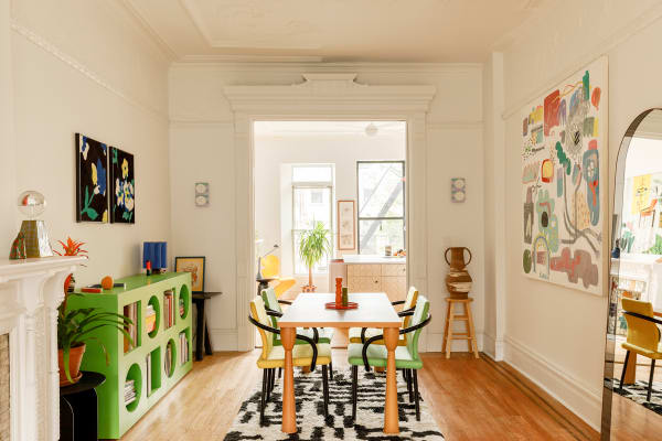 """Herzstück des Essbereichs bilden der Tisch und die Stühle von Ettore Sottsass (Funde von Craigslist und Ruby Lane) sowie ein Prototyp für einen Teppich von Dusen Dusen. Eine Lampe von Bzippy & Co. ziert den Kaminsims. Die Bilder stammen von Kindah Khalidy (rechts) und Matthew Chambers (links). Ein S-Spiegel von Bower lehnt an der rechten Wand, auf einem Hocker steht ein Keramikgefäß von Helen Levi. Und die Wandleuchten? """"Die Leuchten aus Edelstahl habe ich in Chinatown gefunden, die Streifen habe ich später selbst hinzugefügt"""", sagt Ellen. """"Sie sollten nur vorübergehend hier hängen, aber dann sind sie doch geblieben."""""""