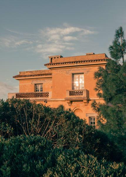"""Das """"Hôtel de la Mer"""" von Rayol wächst hinter den tiefgrünen Bäumen empor."""