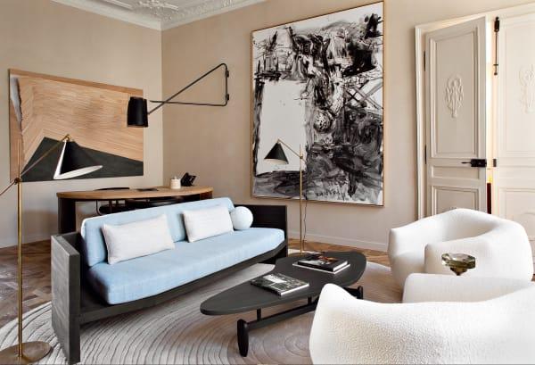 """Salon mit Yovanovitchs Sessel """"Assis(asy)métrie"""", seinem Eichensofa mit lichtblauen Polstern und John Keals Tisch """"Boomerang""""."""